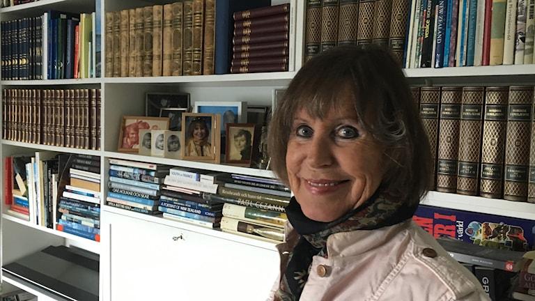 Leende Katarina Bartholdsson framför sin bokhylla.