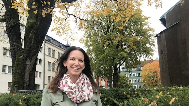 Kvinna står utomhus framför träd