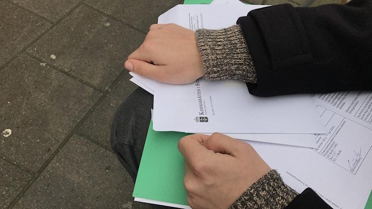Foto på en mans händer som håller i dokument från kammarrätten och Migrationsverket.