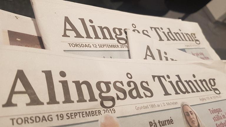 Närbild på en hög med Alingsås tidningar.