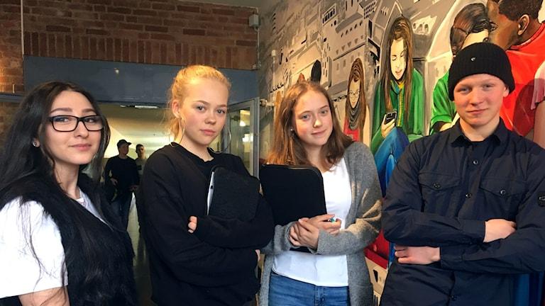 Från vänster: Lara Aziz, Vera Hamnebo, Linnéa Björsson och David Palmén. Alla elever på Engelbrektskolan i Borås, de står inne på skolan och till höger om dem syns en stor väggmålning av ungdomar som studerar.