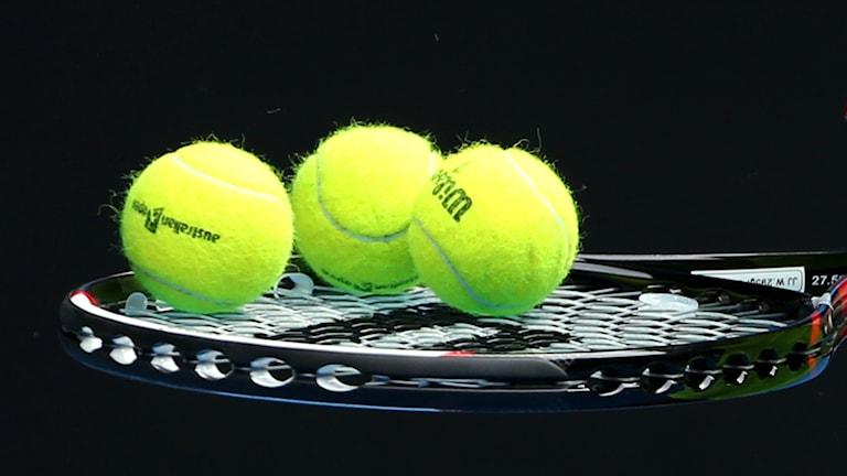 Tre tennisbollar på ett racket.
