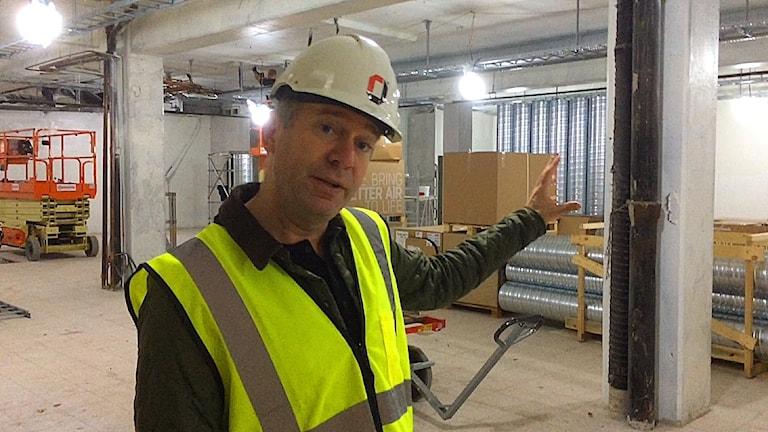 Åke Englund står på en byggarbetsplats med hjälm och reflexväst