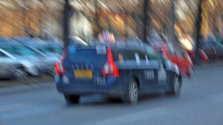 Taxibil med blurrad bakgrund.