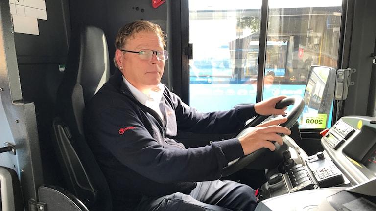 busschaufför i bussen, håller i ratten