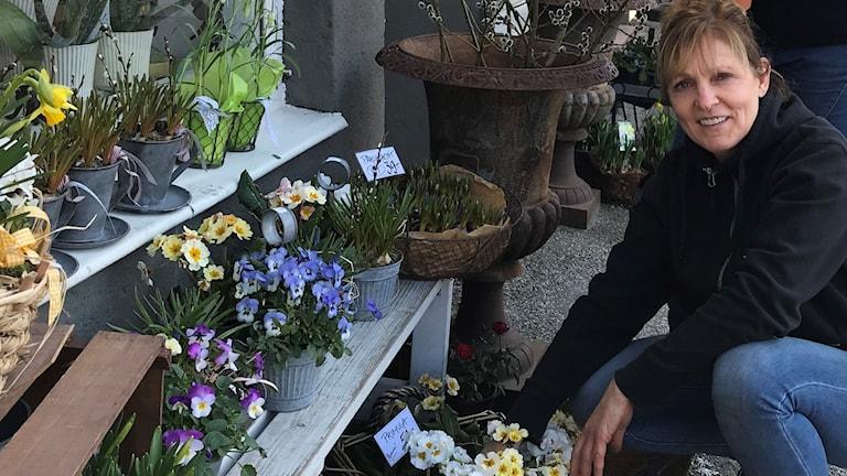 Kvinna med blommor utanför blomaffär