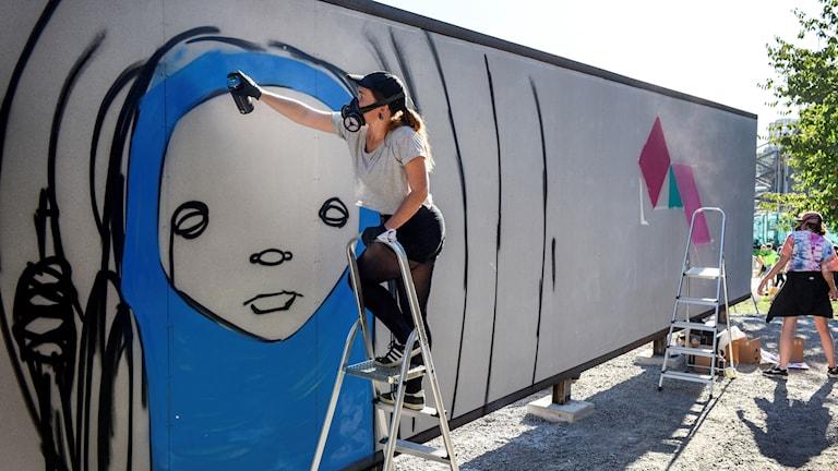 Människor målar på en graffitivägg