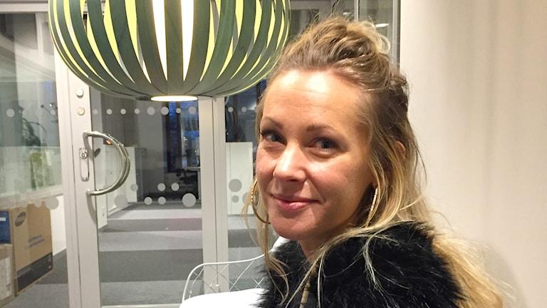 Profilbild på Magdalena Stenlund utanför studion. Stor lampa i bakgrunden. Hon ler lite.