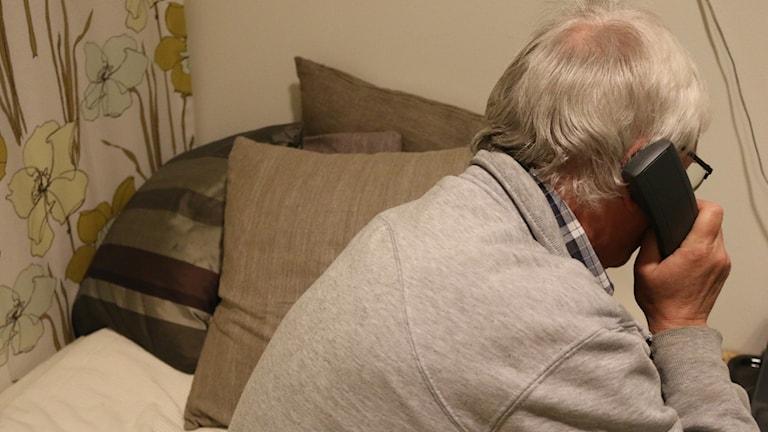 Äldre man sitter på en sängkant med telefonluren mot örat
