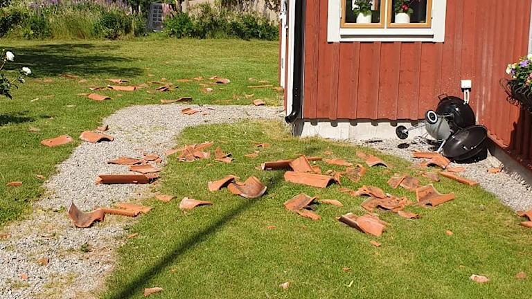 Tegelpannor ligger sönderslagna på gräsmattan efter att stoftvirveln dragit fram.