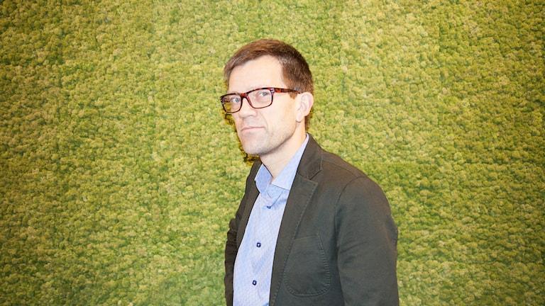 Mattias Goldmann står framför en vägg med en tapet som ser ut som grön mossa.