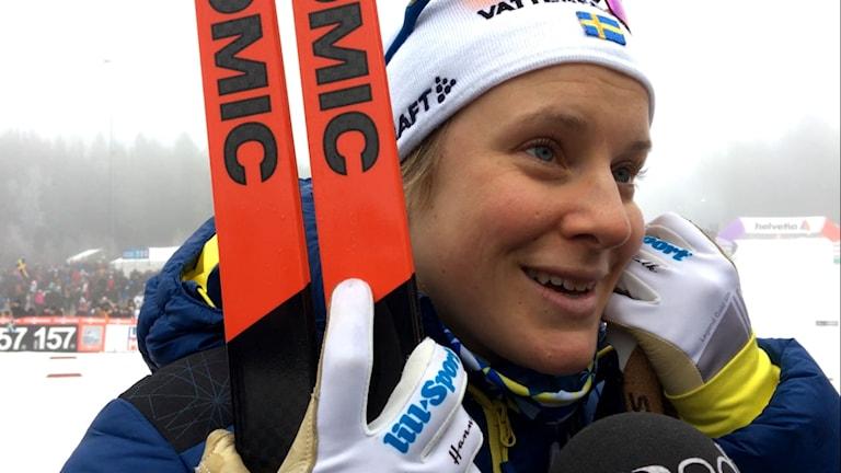 Hanna Falk står med skidor i ena handen och stavar i andra, bakom syns lite av skidspåren och publikmassan på Lassalyckan i Ulricehamn.