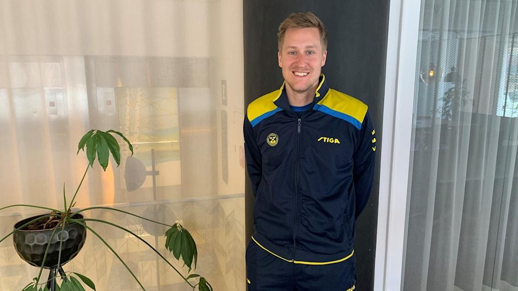 Mattias Falck står framför en vägg.