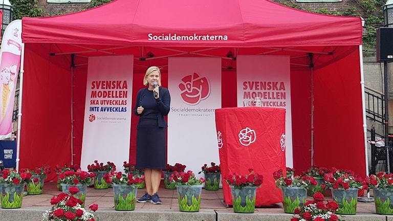 Magdalena Andersson står på en scen och pratar i mikrofon under ett rött tält som det står socialdemokraterna på.