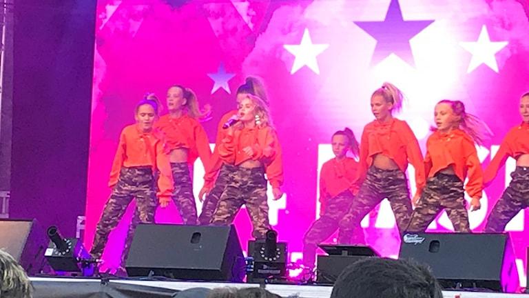 Saga på sång med sex dansare i orange topp och leopardmönstrade byxor.