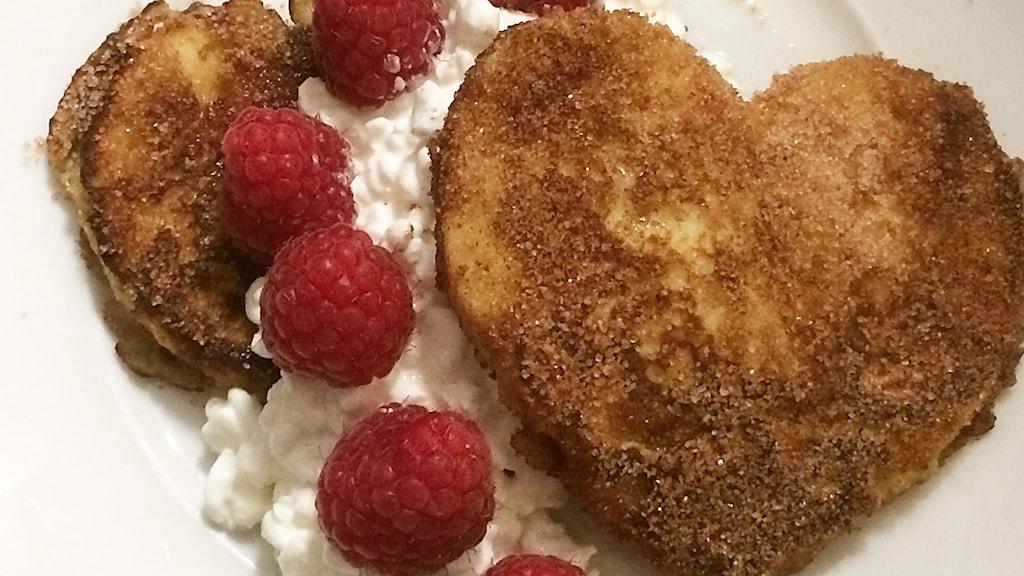 Hjärtformade brödbitar stekta i ägg och smör, med färskost och hallon.