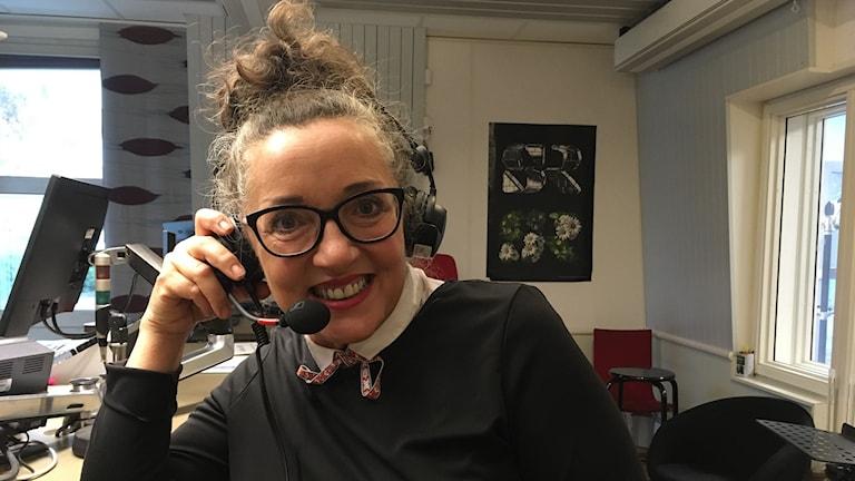 Kvinna sitter i radiostudio med headset på huvudet