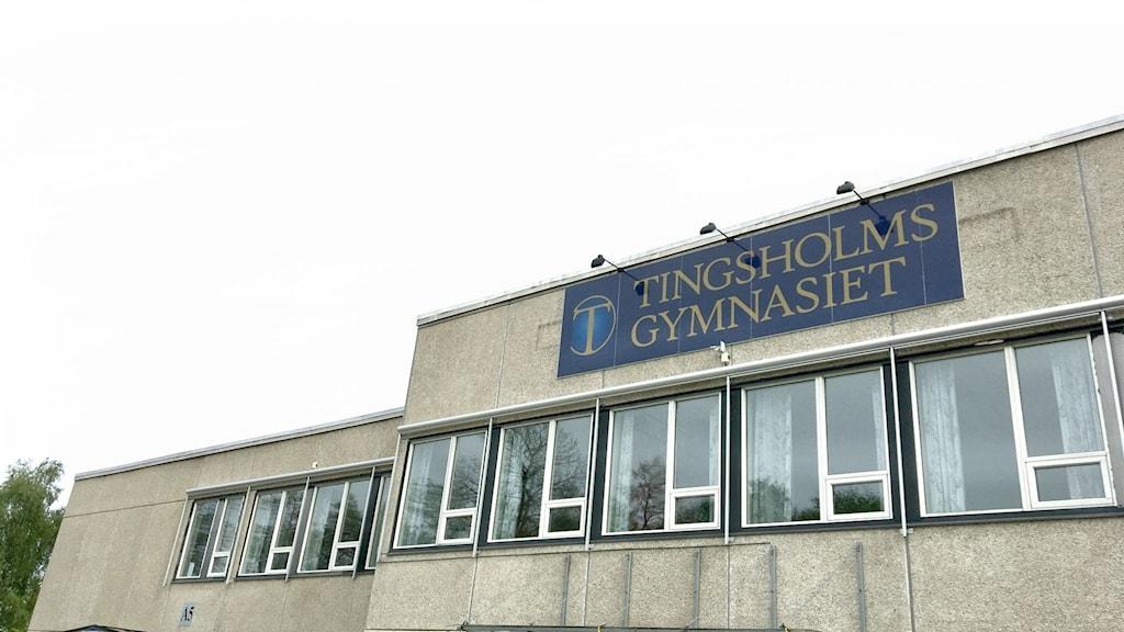 """Fasaden på Tingsholmsgymnasiet mot en vit himmel. Fasaden är grå, i sten med fösnter med vita och svarta karmar. på en mörkblå skylt står det """"Tingsholmsgymnasiet"""" i guldfärgade versaler."""