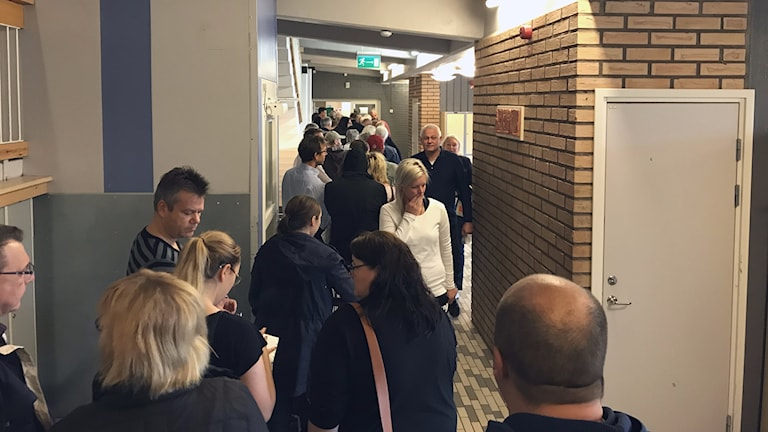 En lång kö i en korridor med personer som ska rösta.