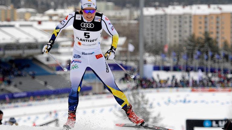 Hanna Falk i vit skiddräkt med gula och blåa partier åker skidor upp för en backe.