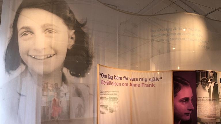 Ett stort, vitt skynke med ett porträtt av Anne Frank täcker större delen av bilden.