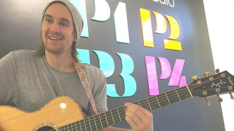 Mathias Melo står med sin gitarr.