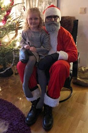 En tomte sitter med ett barn i knät vid en julgran