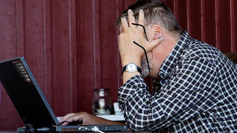 Äldre man i sjuttioårsåldern sitter på  veranda och grubblar över sin dator.