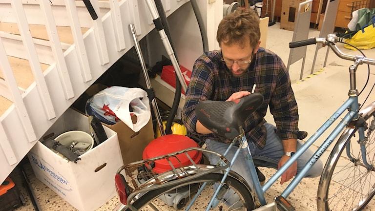 Man i glasögon sitter hukad bakom en cykel
