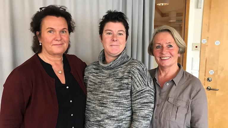 Tre kvinnor står bredvid varandra i ett rum.