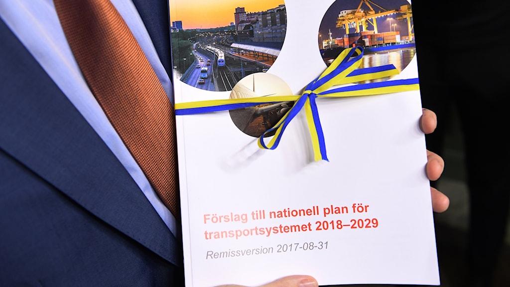 En hand håller i rapporten som har ett band knutet runt i svenska flaggans färger.