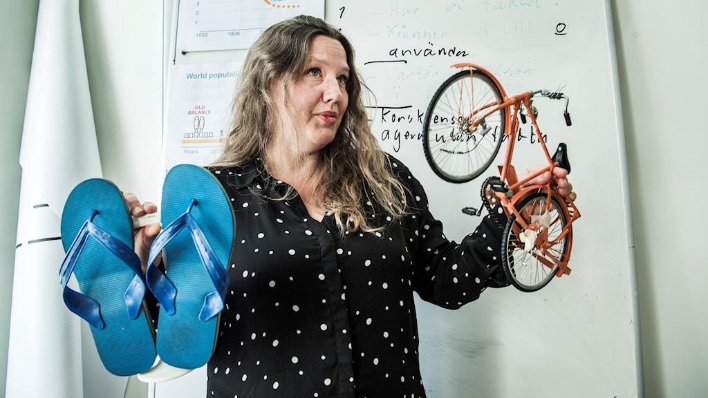 Anna Rosling Rönnlund med sandaler och cykel i händerna.