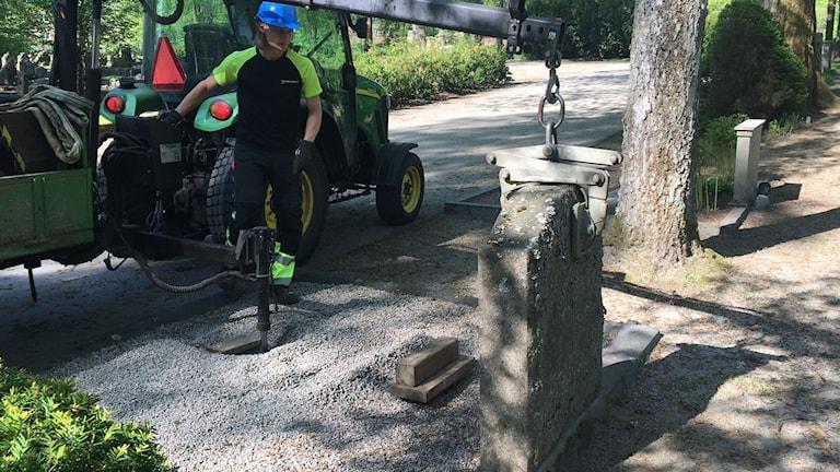 Man vid traktor på kyrkogård. Mannen heter Tomas Kallin och jobbar på kyrkogårdarna i Borås med att säkra gravstenar.