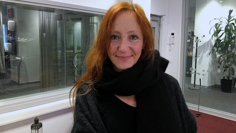 Konstnären Eva Hild i radiostudion. Rött långt hår, mörk kofta och halsduk. Ler med stängd mun.