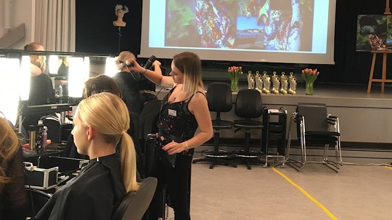 Tävlingar pågår vid Almåsgymnasiet i Borås. Kvinna i ljust hår samt frisör som torkar håret på kvinna.