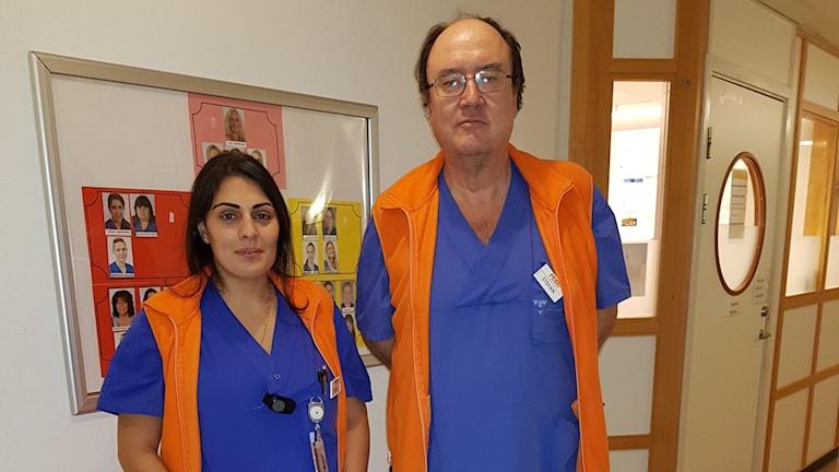 En kvinna och en man står i en korridor på en avdelning framför en anslagstavla. Båda har orangea västar som ska signalera att de är peer supporters