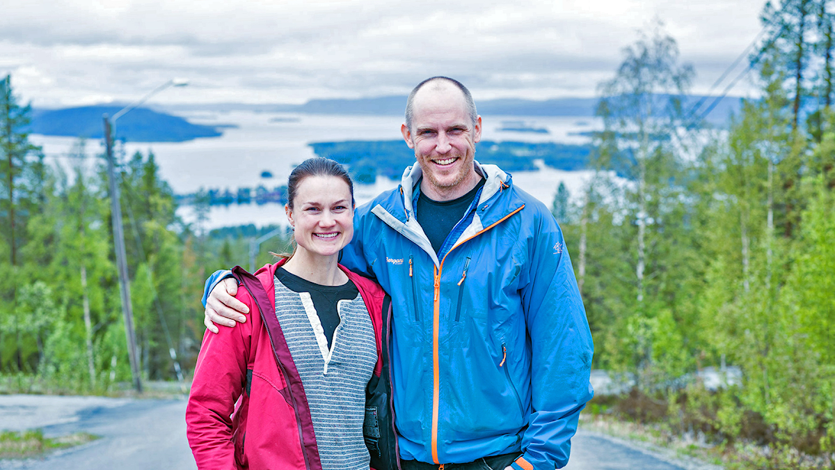 Heidi Andersson och Björn Ferry ler stort mot kameran. Heidi bär en röd jacka och Björn en blå. Björns arm ligger över Heidis axlar. I bakgrunden syns en utsikt över vattnet och öar.