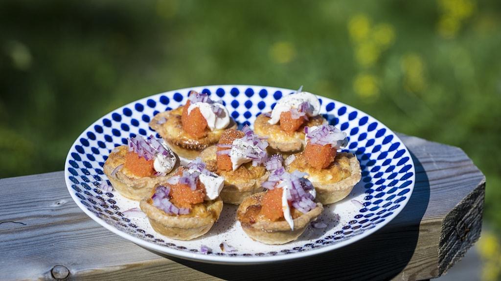 Små västerbottenostpajer på ett fat toppade med löjrom, rödlök och crème fraiche.