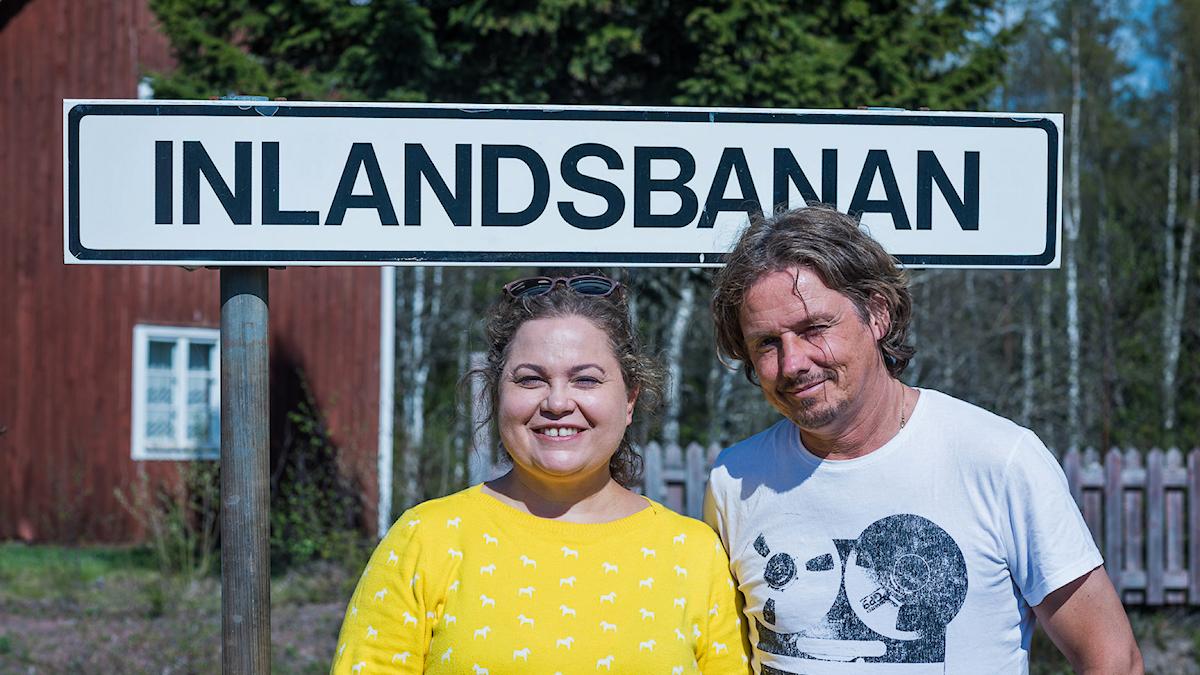 """Susanne och Gerhard står framför den svartvita skylten där det står """"inlandsbenen"""" med stora bokstäver."""
