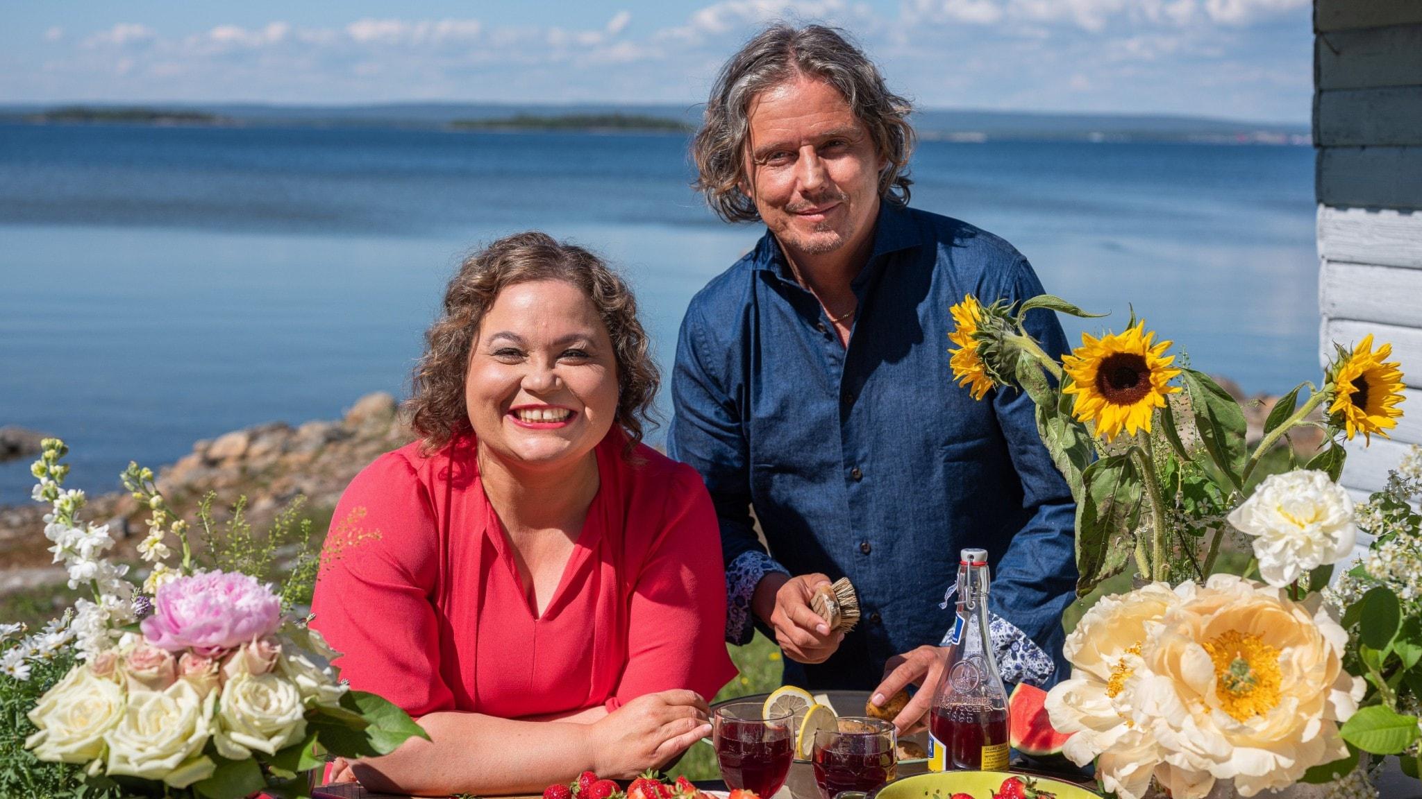 Programledare Susanne Jonsson och Gerhard Stenlund står framför ett bord uppdukat med blommor och tårta, med havet i bakgrunden.