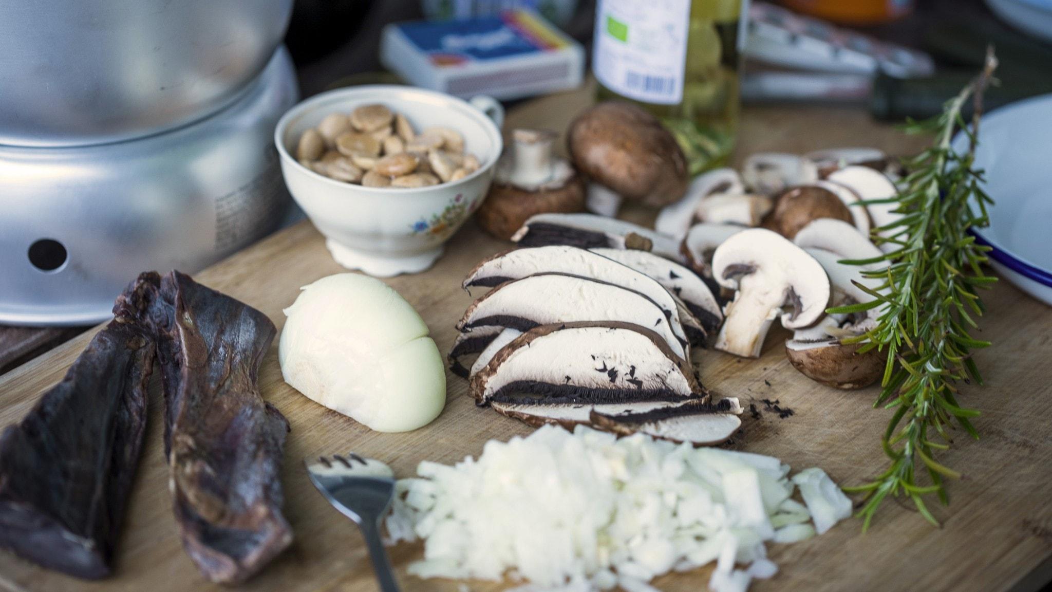 Skärbräda med uppskuren svamp, lök och ingredienser till risotto.