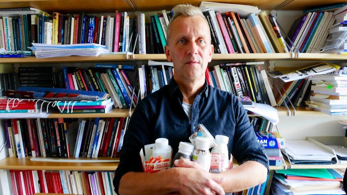 Göran Eriksson, professor i medie- och kommunikationsvetenskap, visar förpackningar som för vidare proteinmyten.