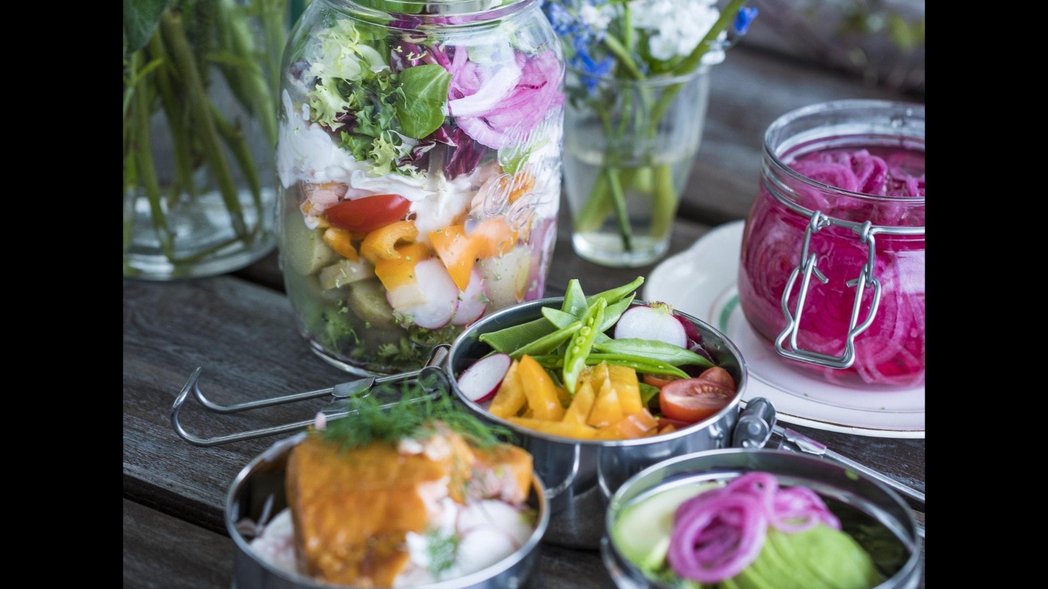 Grönsaker, lax och sallad packade i lådor för picknick.