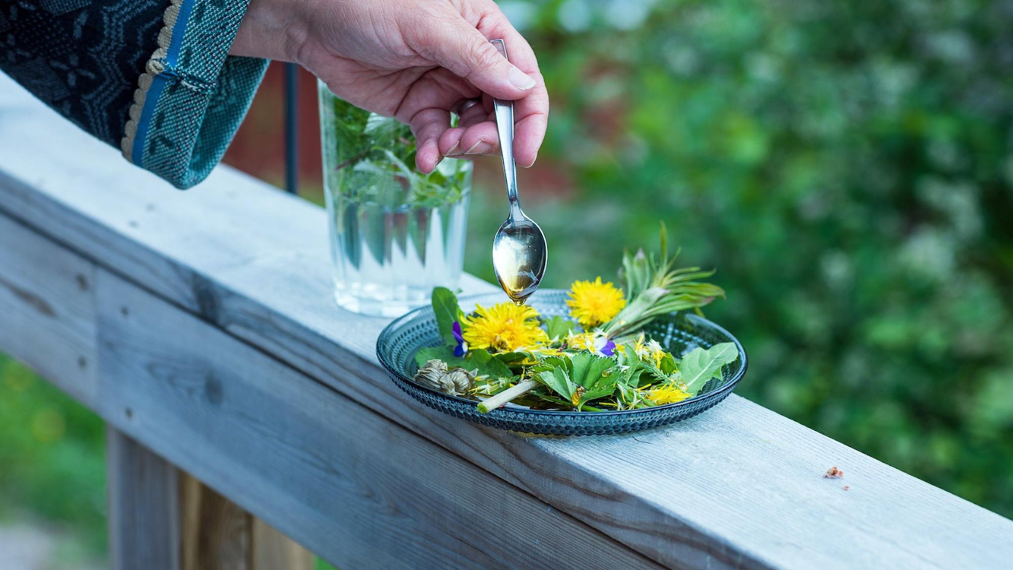 En tallrik med örter och ätbara växter och blommor från naturen står på en träbänk. En bakgrunden står ett glas med iste och en hand som med en sked ringlar honung över örterna.