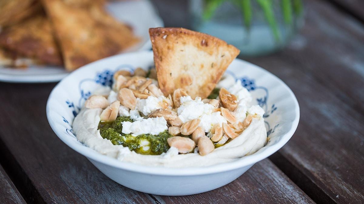 En skål med hummus, pesto, nötter och tunnbrödschips.
