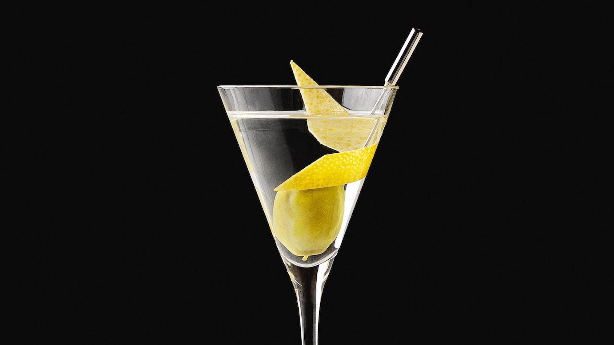 Klassisk dry martini med oliv och citronskal i trekantigt glas.