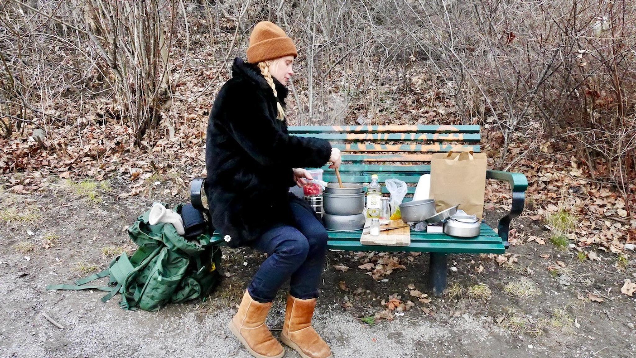 Malin Mendel lagar indisk mat på en parkbänk vid Årstaviken i Stockholm. På ett spritkök.