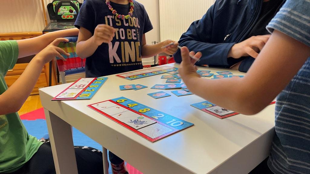 Barn som spelar spel runt bord.