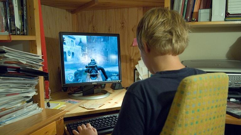 Blond pojke sitter med ryggen mot kameran vid en dator. Skärmen visar ett spel.