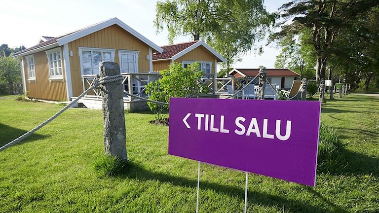 En lila till salu-skylt framför ett hus.